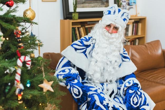 Lustiger weihnachtsmann in einem blauen pelzmantel sitzt in seinem haus am weihnachtsbaum.
