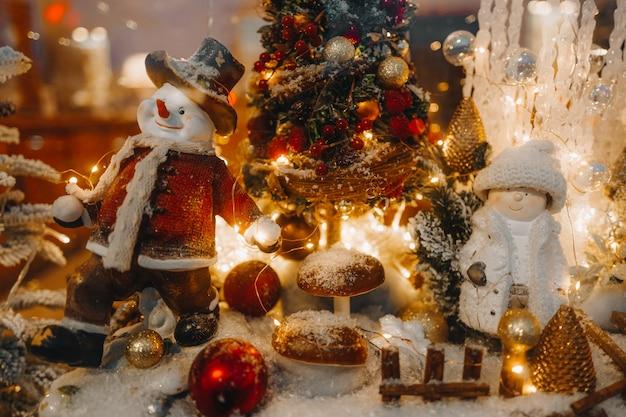 Lustiger winterspielzeugschneemann und schneebedeckter weihnachtsbaum mit goldenen lichtern auf einer festlichen schaufensterfront