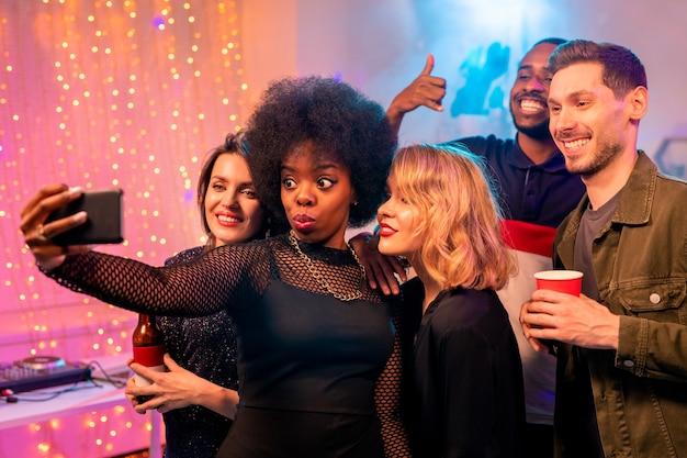 Lustiges afrikanisches mädchen mit gewelltem haar und ihren freudigen freunden, die smartphone-kamera betrachten, während selfie zu hause party machen