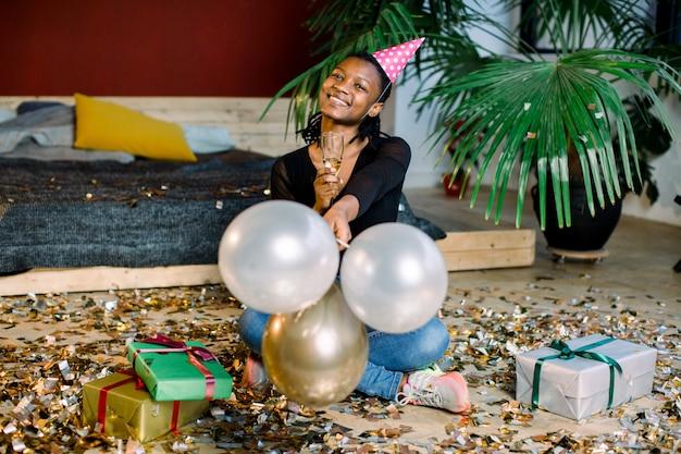 Lustiges afroamerikanisches mädchen im geburtstagshut und mit luftballons, die auf dem boden mit geschenken der geschenkboxen und konfetti sitzen. feier, partykonzept