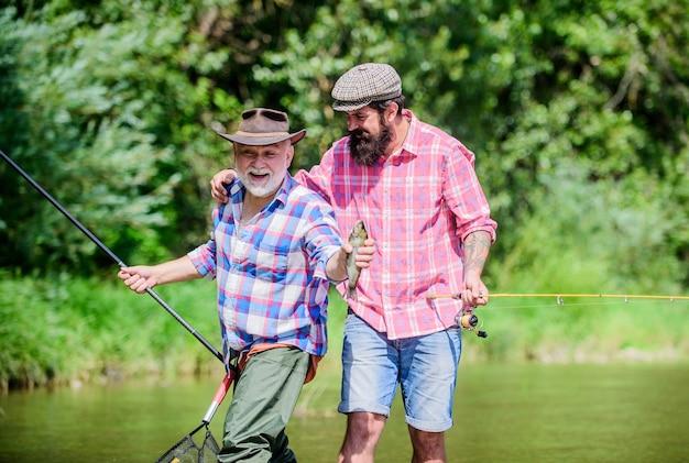 Lustiges angeln. männerfreundschaft. familiäre bindung. zwei glückliche fischer mit angelrute und netz. vater und sohn angeln. sommerwochenende. reife männer fischer. hobby und sportliche betätigung. forellenköder.