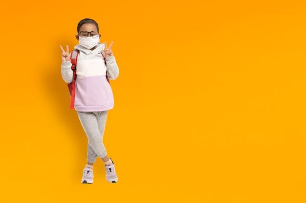 Lustiges asiatisches kindermädchen, das medizinische masken auf gelbem hintergrund trägt