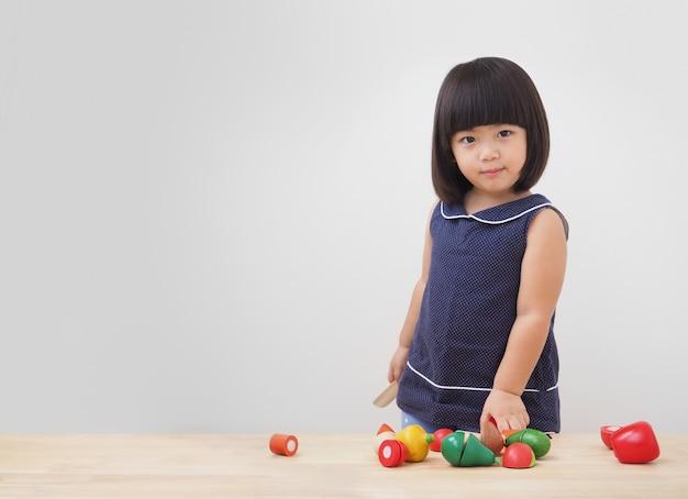 Lustiges asiatisches kindermädchen, das mit hölzernem kochendem spielzeug, kleiner chef zubereitet lebensmittel auf küchenarbeitsplatte spielt.