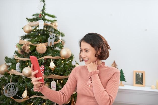 Lustiges asiatisches mädchen, das zu hause in der nähe des weihnachtsbaums selfie-bilder auf der smartphone-kamera macht
