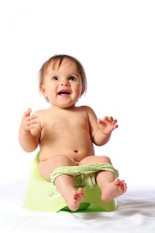 Lustiges baby, das auf grünem töpfchen sitzt