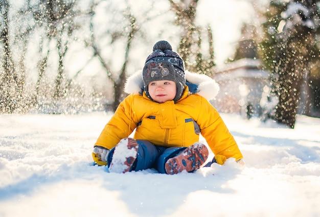 Lustiges baby, das draußen am wintertag lacht