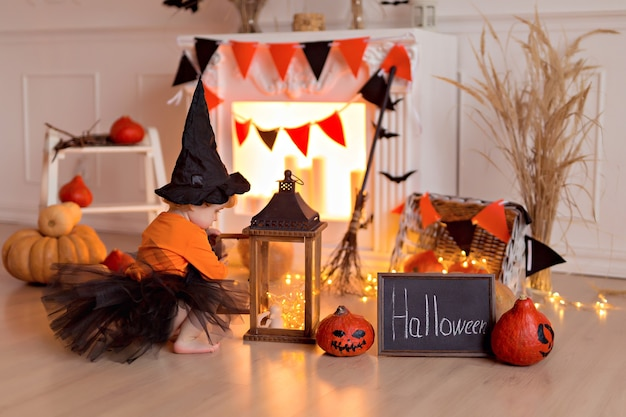Lustiges baby im halloween-hexenkostüm mit kürbisheber und besen drinnen