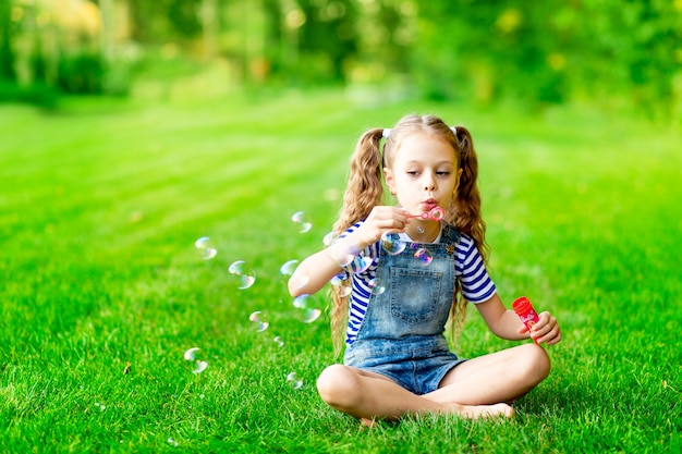 Lustiges baby im sommer auf dem rasen mit seifenblasen auf dem grünen gras, spaß und freude, platz für text