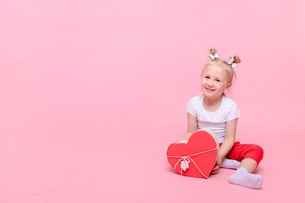 Lustiges baby in einem weißen t-shirt und in der roten hose mit einer herzförmigen schachtel auf einem rosa hintergrund.