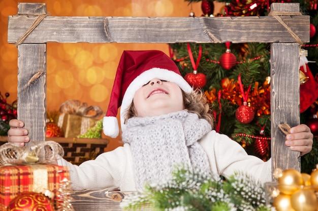 Lustiges baby in santas hut mit holzrahmen gegen weihnachtsbeleuchtung hintergrund