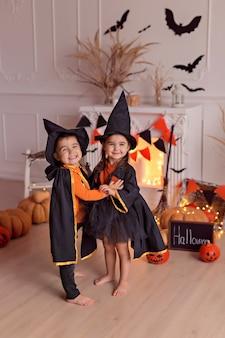 Lustiges baby und mädchen im halloween-hexenkostüm mit kürbisheber und besen drinnen