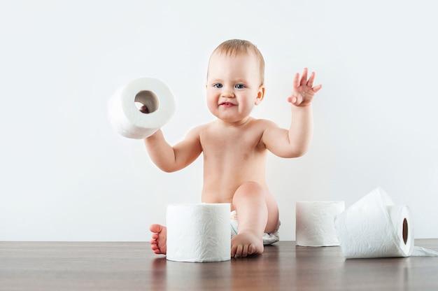 Lustiges baby und toilettenpapier auf weißer wand. kleinkind zerreißt toilettenpapier. üben aufs töpfchen zu gehen