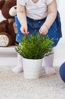 Lustiges babykleinkindmädchen, das im wohnzimmer spielt. kinder- und familienkonzept. nahansicht.