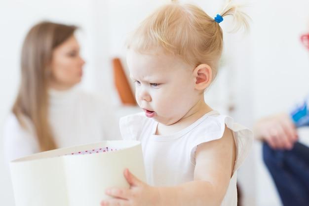 Lustiges babykleinkindmädchen, das im wohnzimmer spielt. kinder- und familienkonzept.
