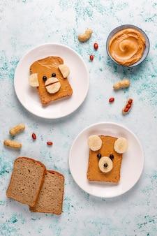 Lustiges bären- und affengesichtssandwich mit erdnussbutter, banane und schwarzer johannisbeere, draufsicht