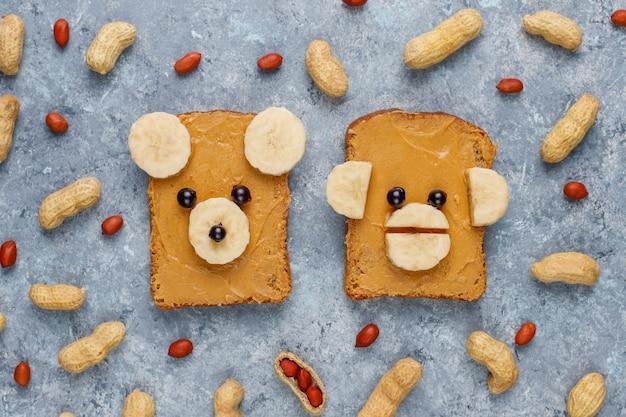 Lustiges bären- und affengesichtssandwich mit erdnussbutter, banane und schwarzer johannisbeere, erdnüsse, draufsicht