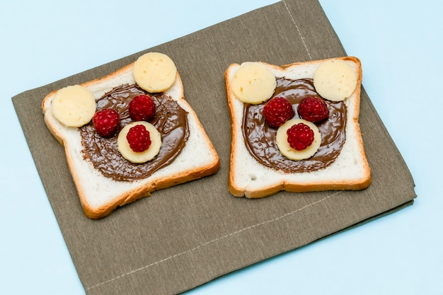 Lustiges bärengesichts-sandwich-toastbrot mit erdnussbutter, käse und himbeere auf blauem hintergrund der serviette. kinder kind süßes dessert frühstück mittagessen essen hautnah