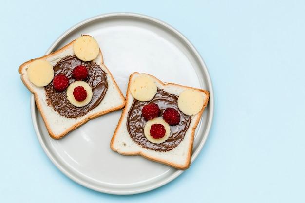 Lustiges bärengesichtssandwichtoastbrot mit erdnussbutter, käse und himbeere auf blauem hintergrund der platte. kinder kind süßes dessert frühstück mittagessen essen hautnah