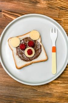 Lustiges bärengesichtssandwichtoastbrot mit erdnussbutter, käse und himbeere auf hölzernem hintergrund der platte. kinder kind süße dessert frühstück mittagessen essen hautnah.