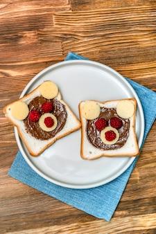 Lustiges bärengesichtssandwichtoastbrot mit erdnussbutter, käse und himbeere auf hölzernem hintergrund der tellerserviette. kinder kind süßes dessert frühstück mittagessen essen hautnah