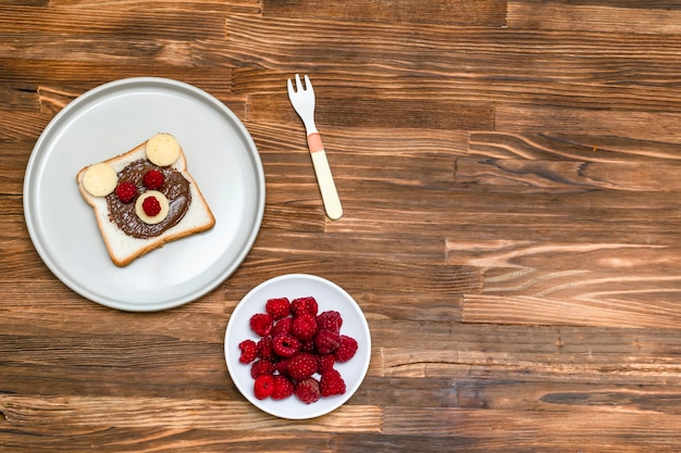 Lustiges bärengesichtssandwichtoastbrot mit erdnussbutter, käse und himbeere auf hölzernem hintergrundkopienraum der platte. kinder kind süßes dessert frühstück mittagessen essen.
