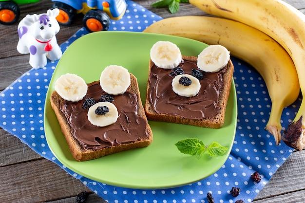 Lustiges bärensandwich mit schokolade, banane und rosinen