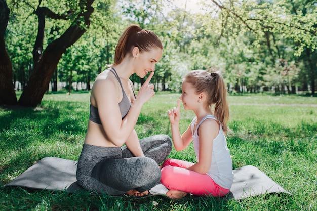Lustiges bild os mädchen, die auf karimat draußen im park sitzen und einander das schweigensymbol zeigen. sie lächeln und lachen ein bisschen. yoga und pilates konzept.