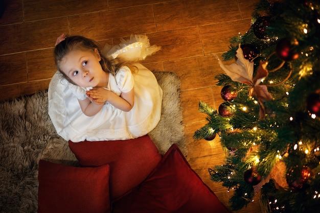 Lustiges blondes engelsmädchen 35 jahre alt, das auf dem boden nahe dem weihnachtsbaum sitzt