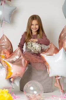Lustiges blondes mädchen unter ballonen und halten eines blumenstraußes der wildblumen