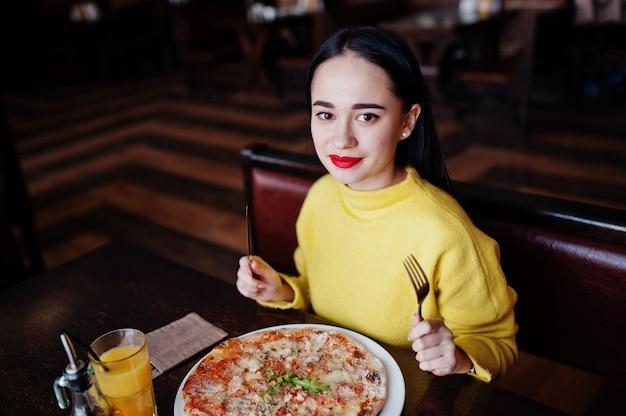 Lustiges brunettemädchen in der gelben strickjacke pizza am restaurant essend.