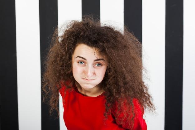 Lustiges brunettemädchenporträt auf gestreiftem hintergrund