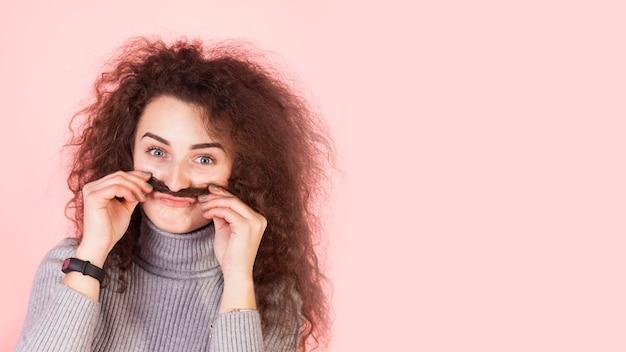 Lustiges brunettemädchenporträt auf rosa hintergrund