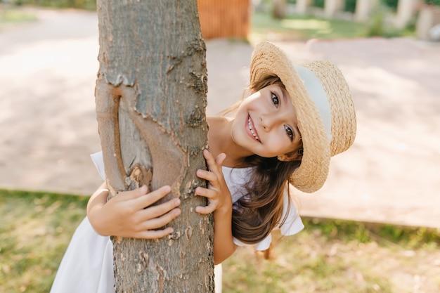 Lustiges dunkelhaariges kind mit großen augen und lächeln, das baum im park umarmt. außenporträt des glücklichen kleinen mädchens im strohhut, das sommerferien genießt.