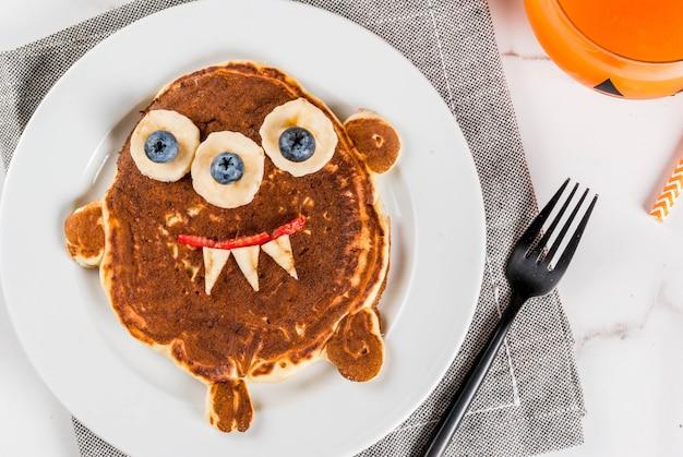 Lustiges essen für halloween. kinderfrühstückspfannkuchen verziert wie gruseliges monster, mit banane, beeren, mit kürbis smoothiesaft, weiße tabelle