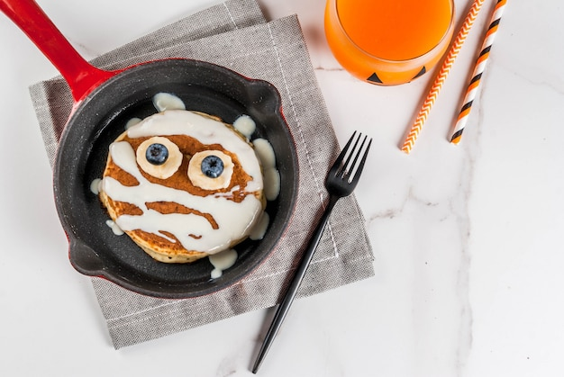 Lustiges essen für halloween. kinderfrühstückspfannkuchen verziert wie mama mit weißer schokoladensoße, banane, beeren, mit kürbis smoothiesaft, weiße tabelle