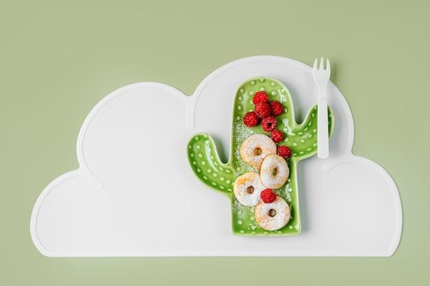 Lustiges essen für kinder. kinderfrühstück. teller in form eines kaktus mit donuts und beeren. essensidee für kinder.
