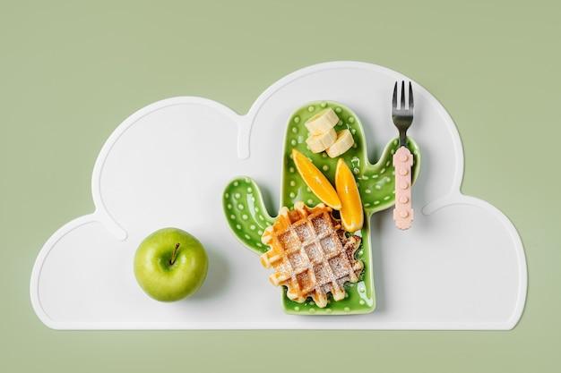 Lustiges essen für kinder. kinderfrühstück. teller in form eines kaktus mit waffeln und früchten. essensidee für kinder.