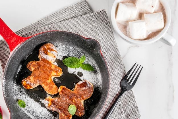 Lustiges essen zu weihnachten. kinderfrühstückspfannkuchen verziert wie lebkuchenmänner, mit heißer schokolade mit eibisch, weiße tabelle