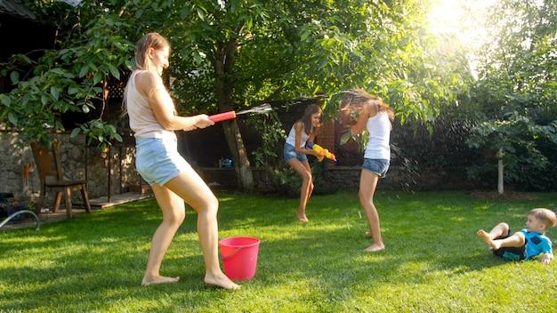 Lustiges foto einer glücklichen familie mit kindern, die am heißen sonnigen tag mit wasserpistolen und gartenschlauch spielen und wasser spritzen