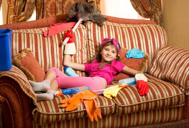 Lustiges foto eines erschöpften mädchens, das sich nach der reinigung des hauses auf dem sofa entspannt