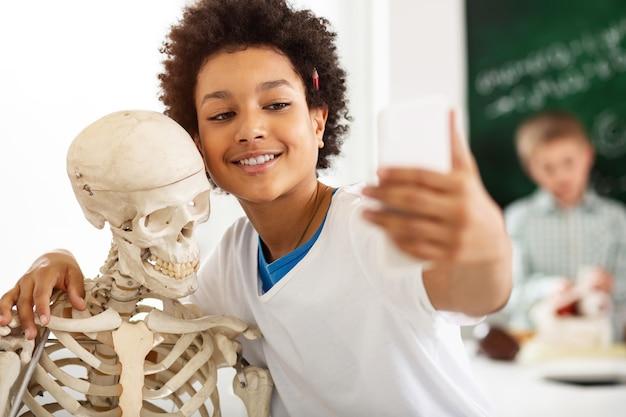 Lustiges foto. fröhlicher glücklicher teenager, der ein skelett umarmt, während er ein lustiges foto macht