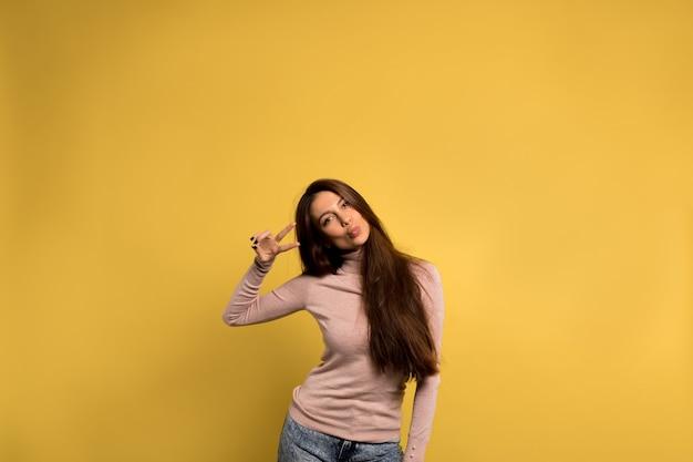 Lustiges freundliches mädchen mit langen braunen haaren, die jeans und rosa hemd tragen, senden einen kuss und zeigen friedenszeichen über gelber wand