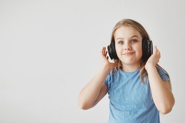 Lustiges fröhliches mädchen mit hellem haar und blauen augen, kopfhörer tragend. mit schockiertem ausdruck, nachdem plötzlich laute musik zu spielen beginnt