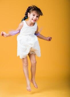 Lustiges fröhliches schönes mädchen springt, das barfuß auf einer gelben wand aufwirft. das konzept der lustigen unruhigen kinder. platz für werbung