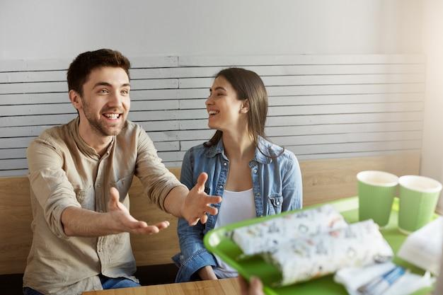Lustiges fröhliches studentenpaar mit dunklem haar, das im café sitzt, über den heutigen vortrag spricht und auf essen wartet, das sie bestellt haben.