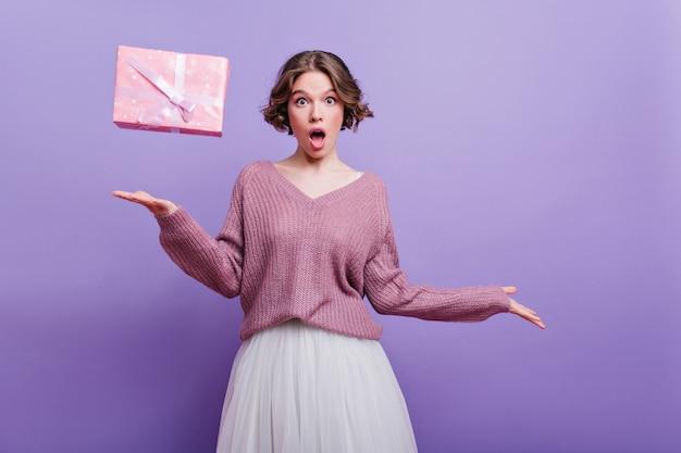 Lustiges geburtstagskind im pullover, das überraschte gefühle auf lila wand ausdrückt. emotionale kurzhaarige dame im weißen rock posiert mit geschenkbox zu hause.