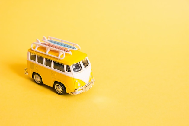 Lustiges gelbes retro- auto mit surfbrett auf gelb
