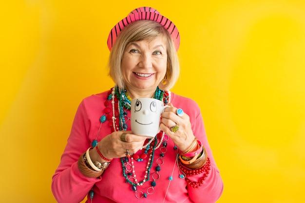 Lustiges gesicht der glücklichen älteren frau, das eine tasse kaffee oder tee in der stilvollen kleidung älterer leute trinkt