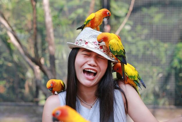 Lustiges gesicht der schönen asiatin, die mit sonne conure papageien spielt.