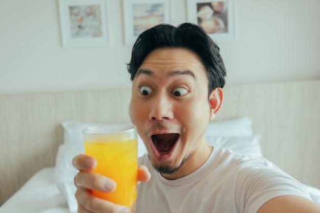 Lustiges gesicht des mannes trinken frischen orangensaft im hotel für den sommerurlaub